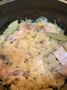 サワークラウトにお肉をいれ、ローリエの葉っぱ、黒胡椒、白ワインを入れたところ